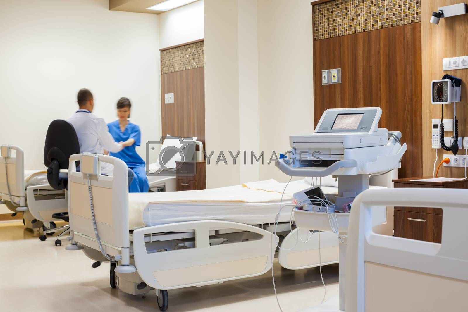 Blurred figure of a patient being helped by a doctor to rise from the bed in a spacy modern hospital room. ECG machine on focus.