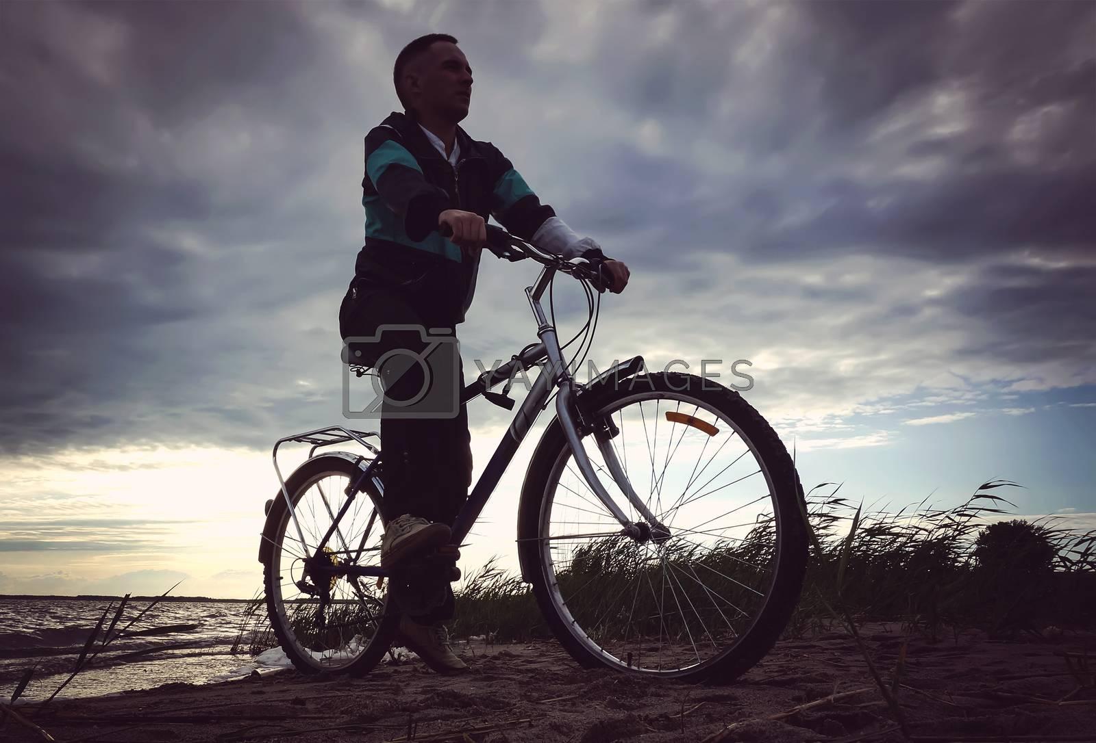 A man rides his mountain bike on a beach. The guy riding on the beach by bike near the lake