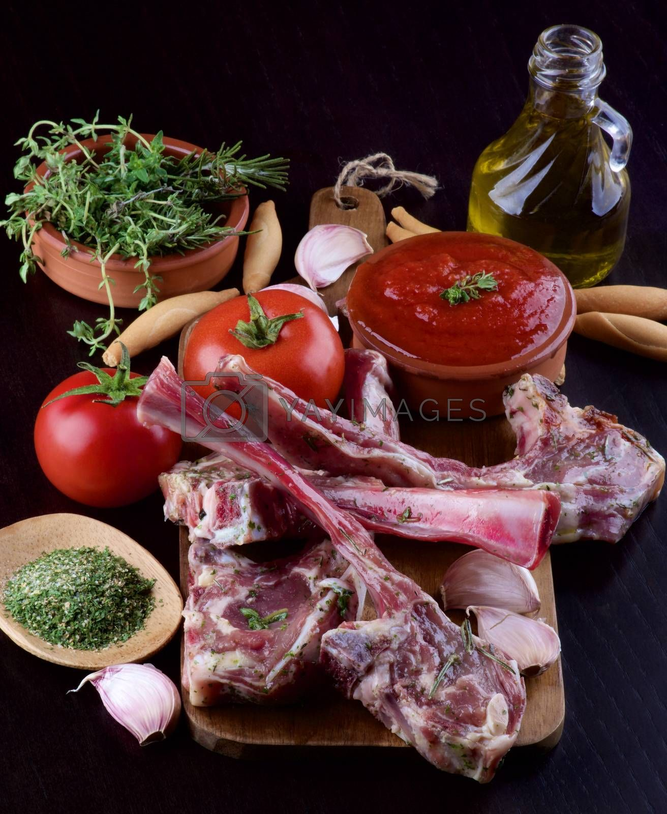Ready to Roast Raw Lamb Ribs with Tomatoes, Sauce, Garlic, Herbs, Spices and Olive Oil on Wooden Cutting Board closeup on Dark Wooden background