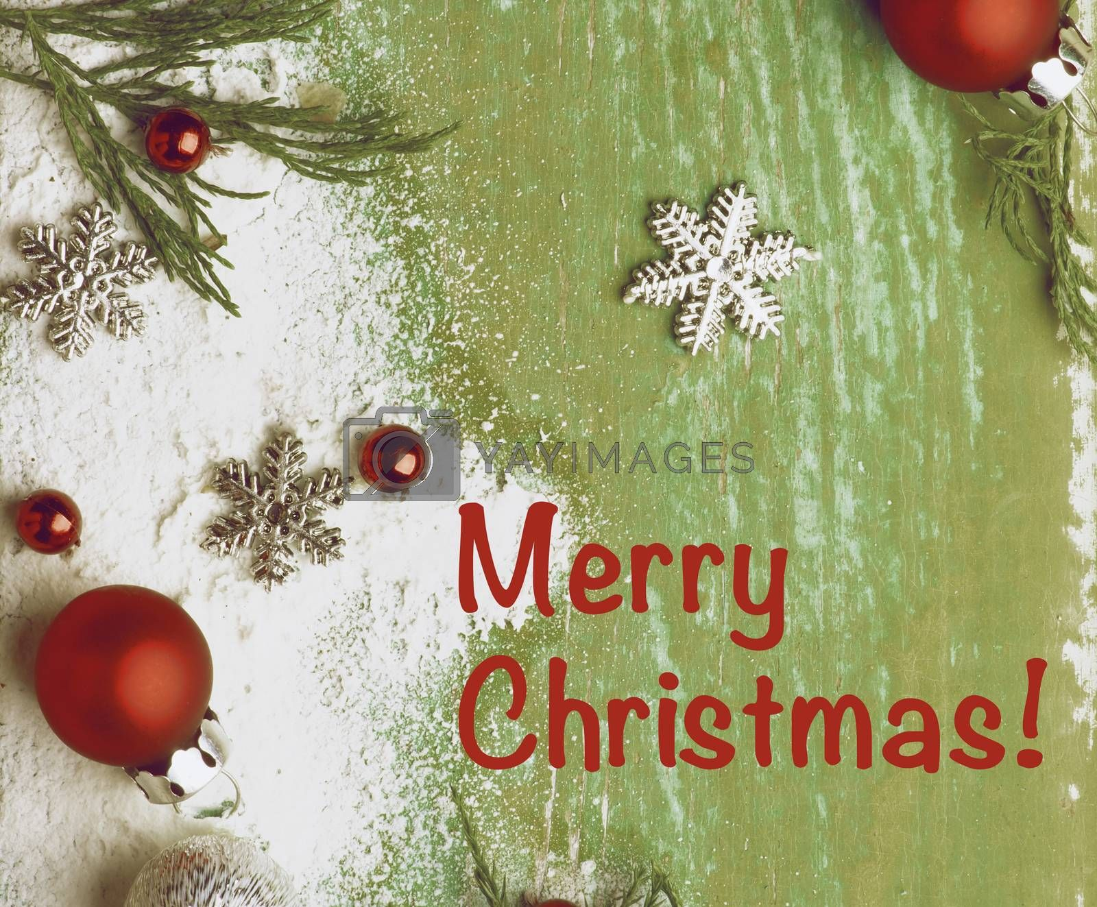 Christmas Greeting Card with Border of Green Branches, Snow Flakes and Decorations with Inscriptions closeup on Cracked Wooden background