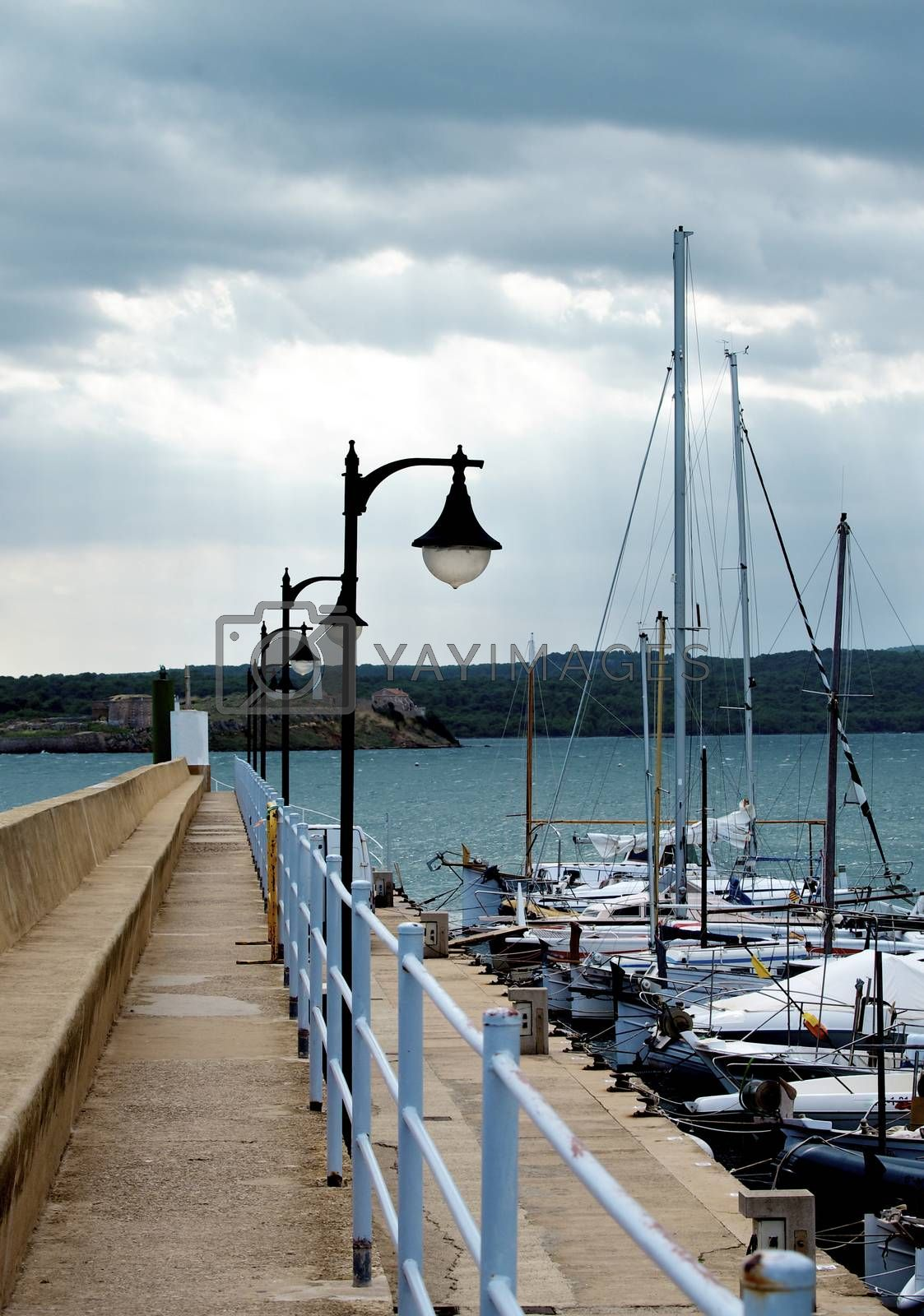 Pier with Street Lamps and Small Sailboats in Marina against Dramatic Sea Outdoors. Menorca, Balearic Islands