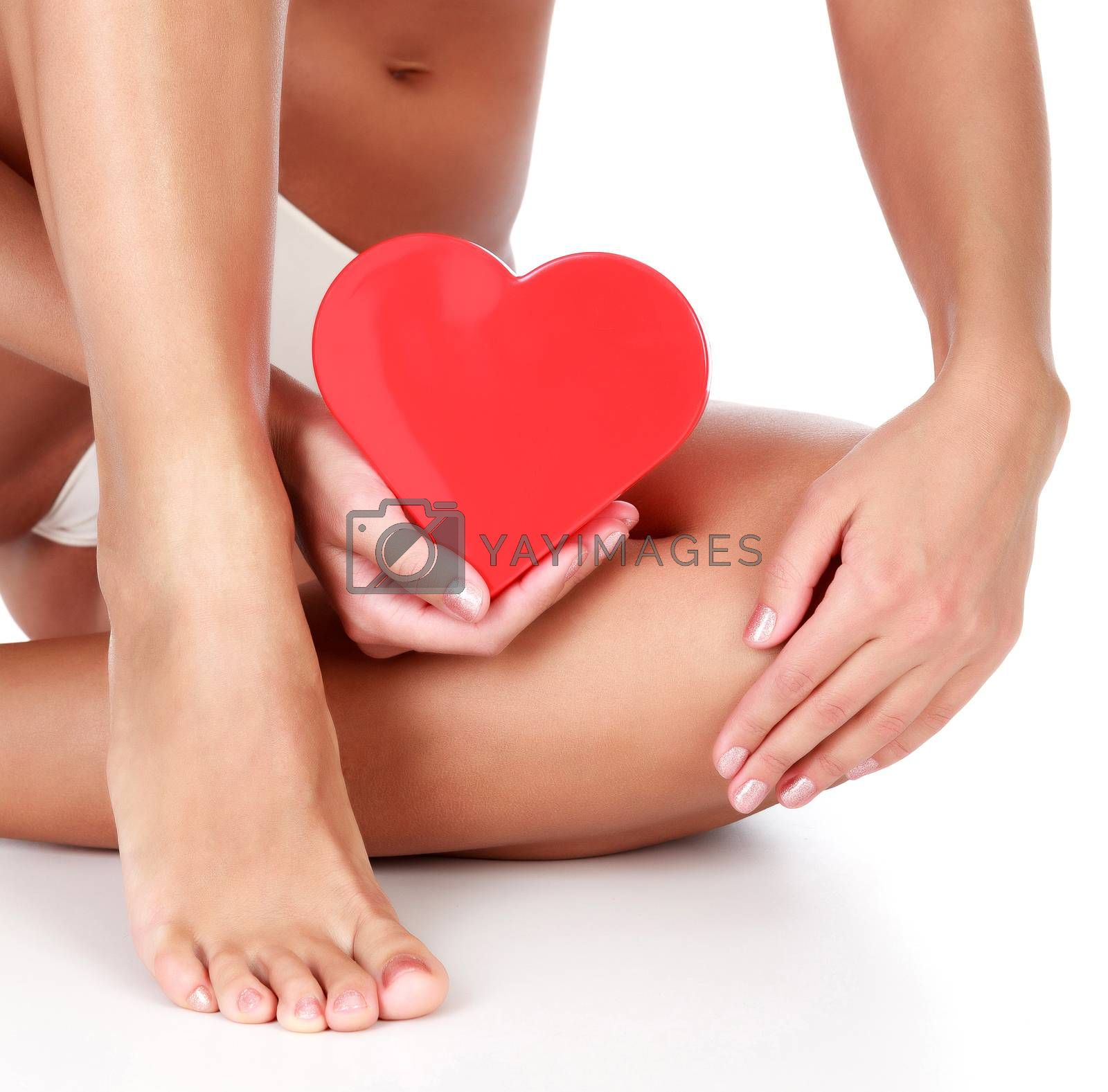 Woman with clean and soft skin holds a red plastic heart.