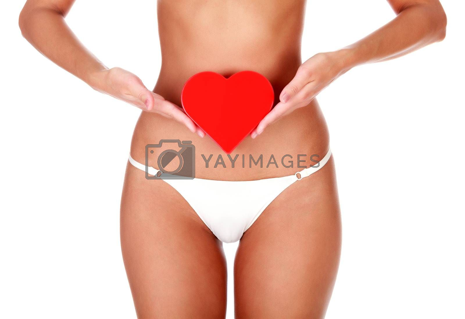 Woman with slim body and healthy skin holds a red plastic heart, isolated on white background