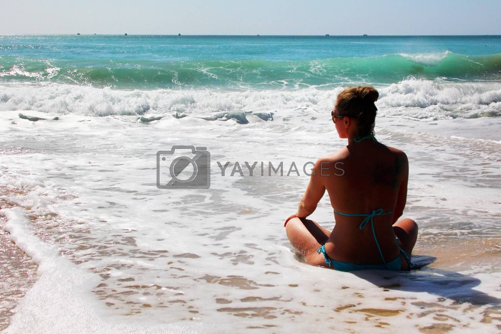 The girl is meditating on the ocean shore. Bali