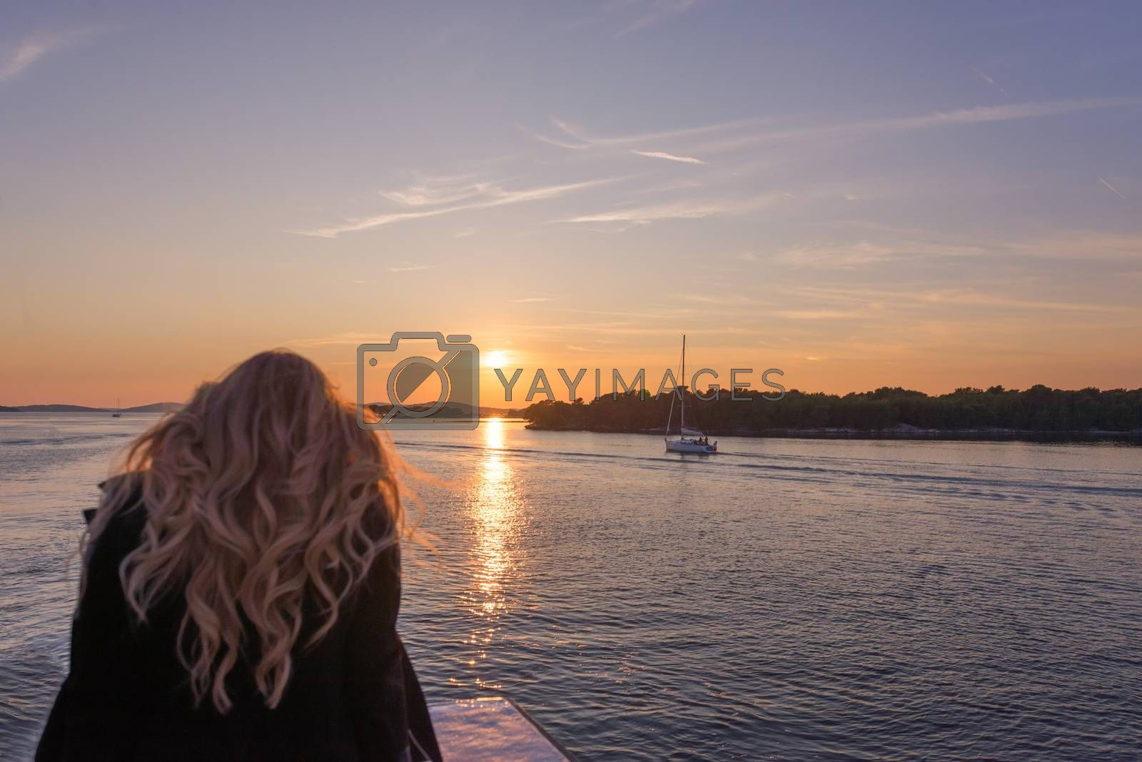 Woman traveling by boat at sunset among the islands, sailing boats and yachts in background