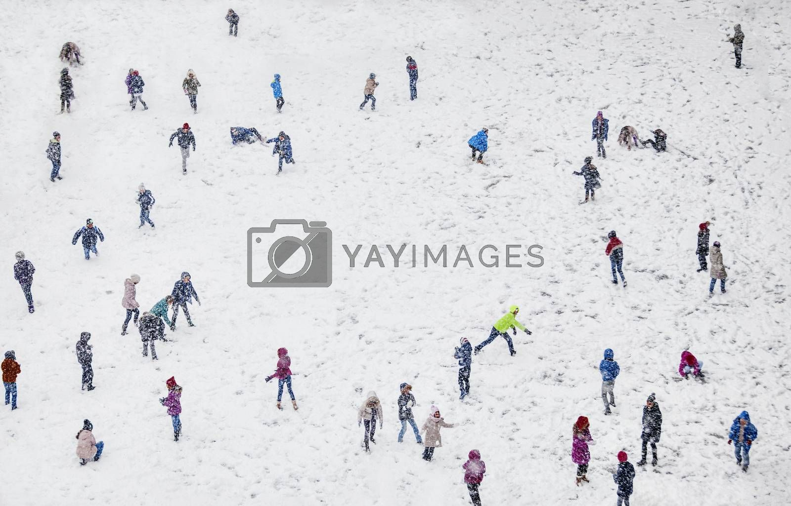 A field during winter, full of playing with the snow children, blurred faces.