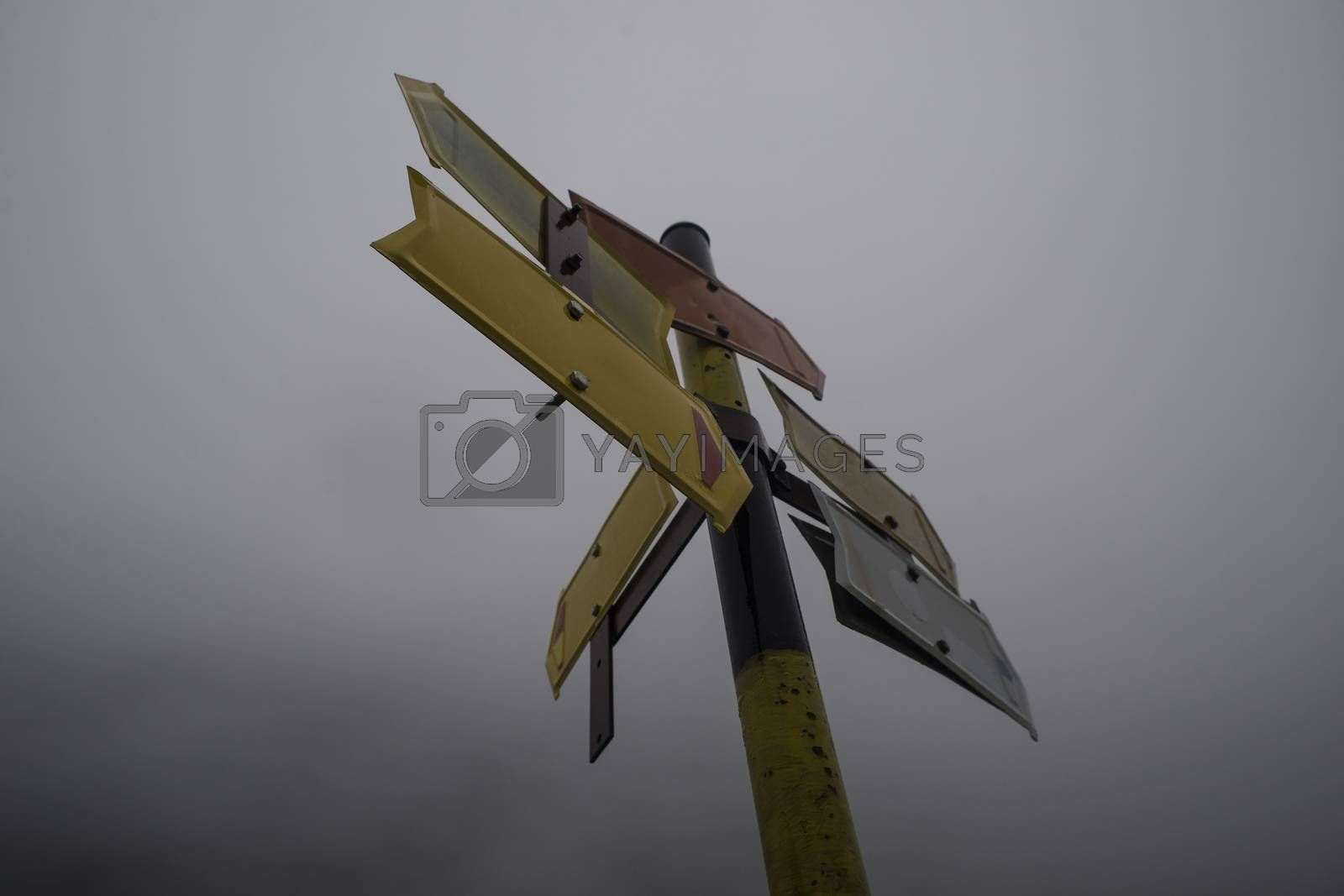 A pole with several, five usable, empty mountain road direction pointers in cold misty weather.