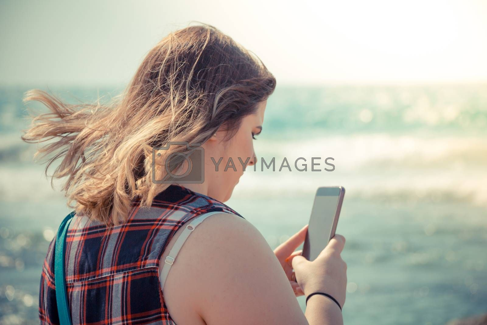 Woman using her smartphone outdoors at the beach near the sea.