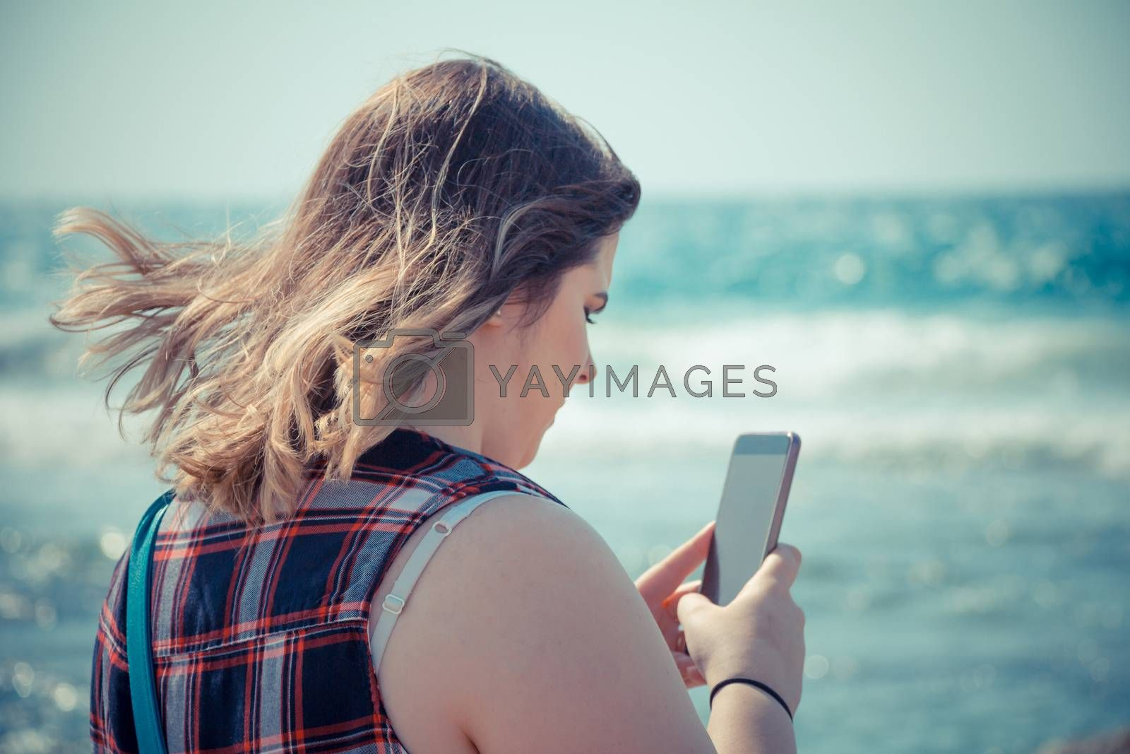 Woman using her smartphone outdoors at the beach near the sea by wavemovies