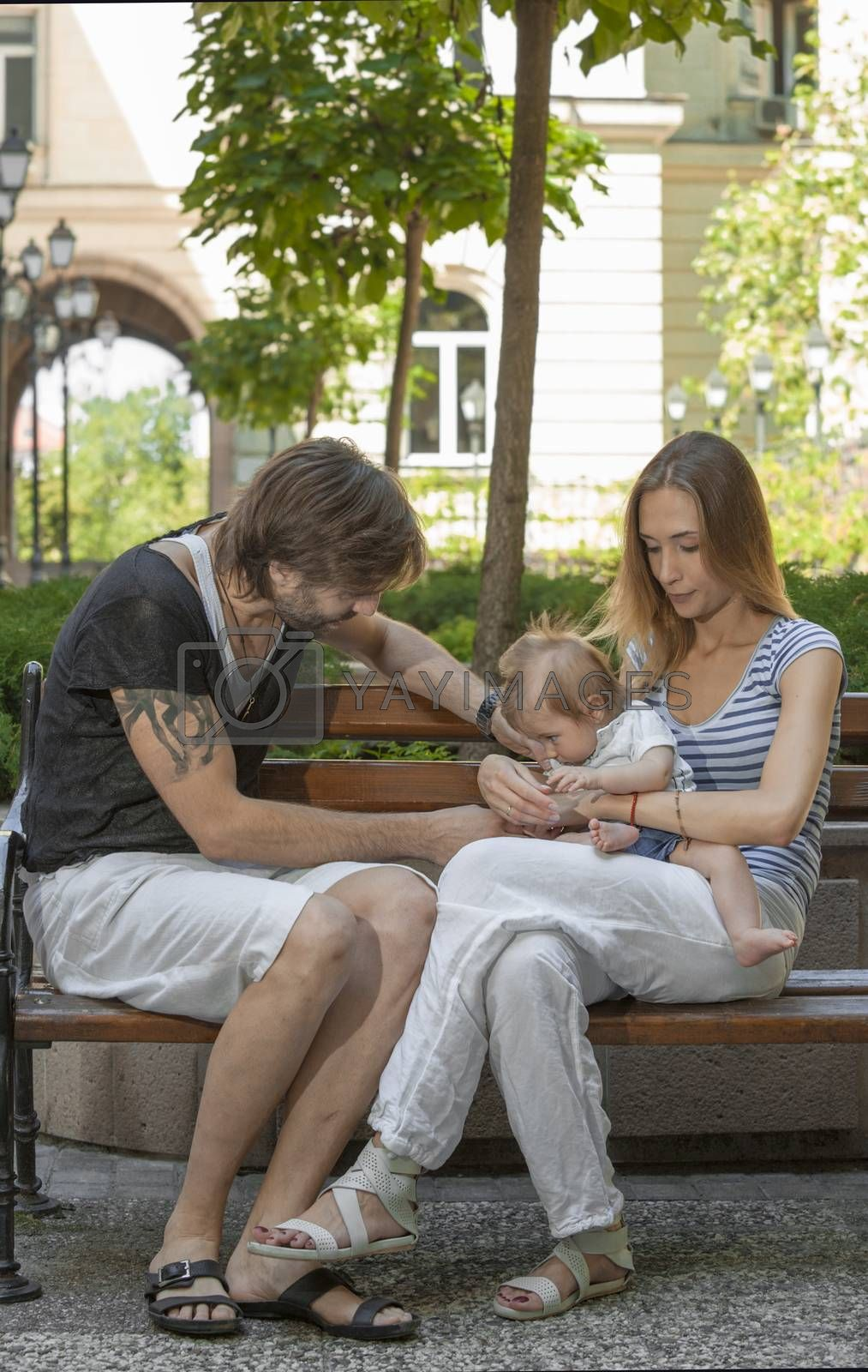 Happy young beautiful family of three is sitting on a bench outdoors in a european city.