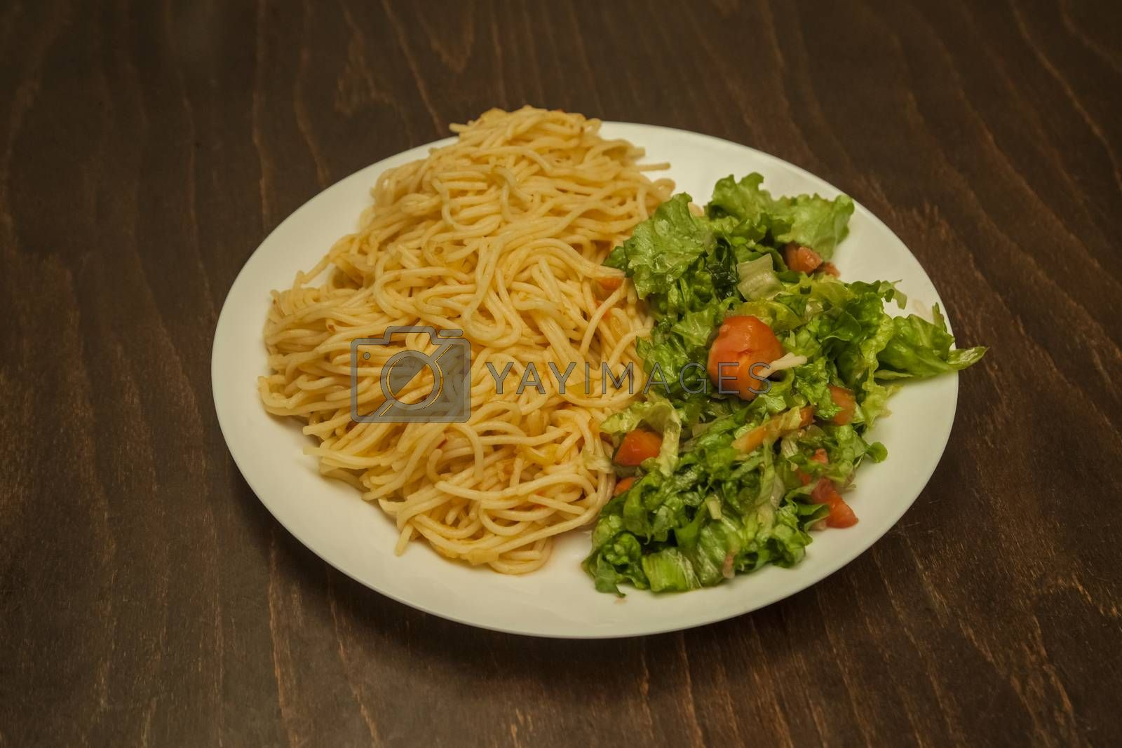 A serving of spaghetti with red sauce and salad.