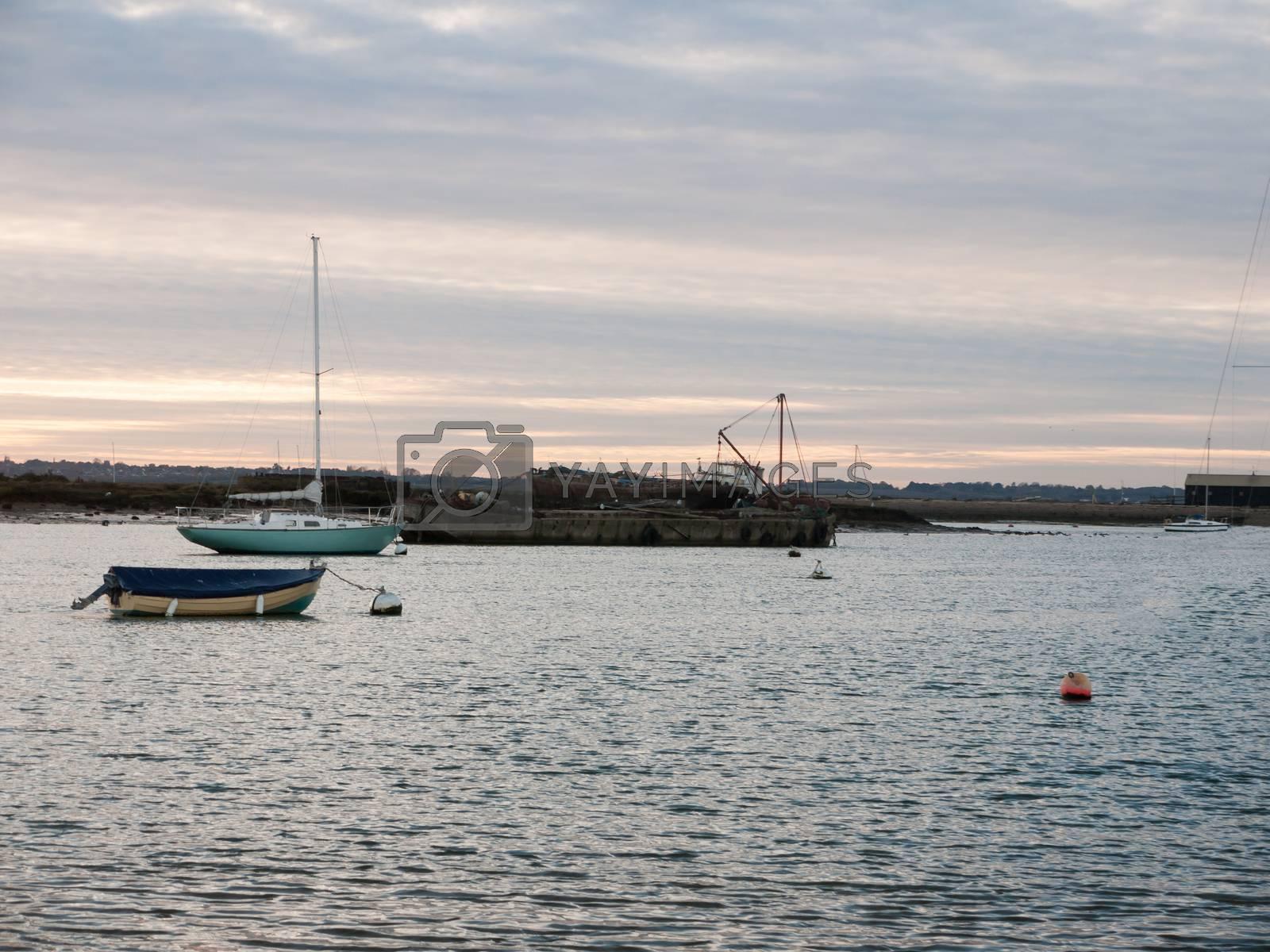 marina harbor ocean moored boats landscape empty sun set space; west mersea, essex, england, uk