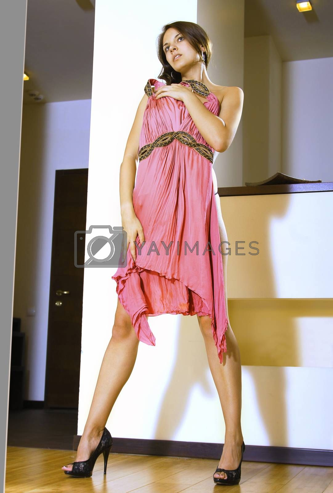 beautiful woman fits on new pink dress in the shopping mall