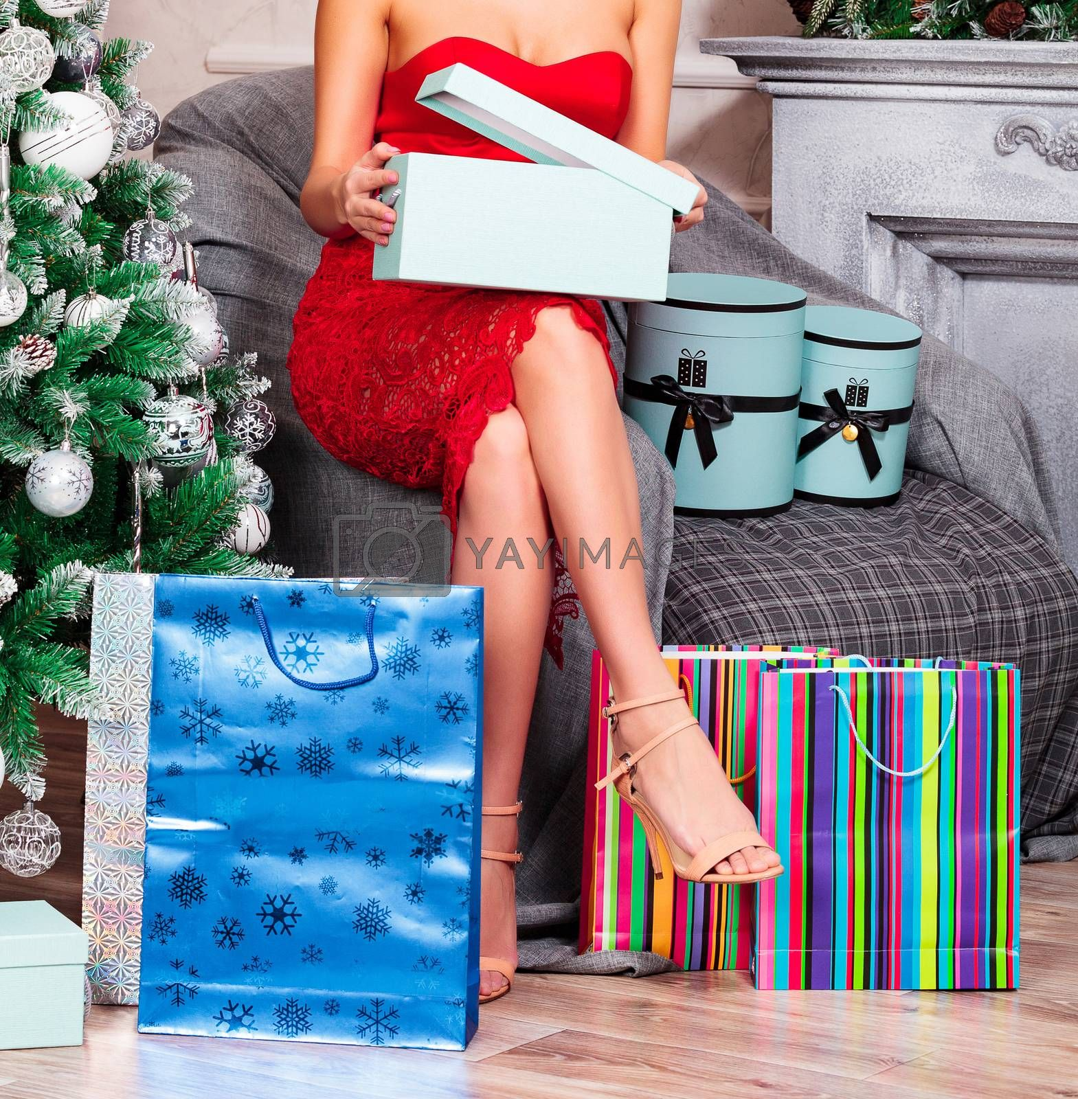 Woman in red dress opening her christmas gift boxes while sitting at home near by christmas tree. Holidays and celebration concept
