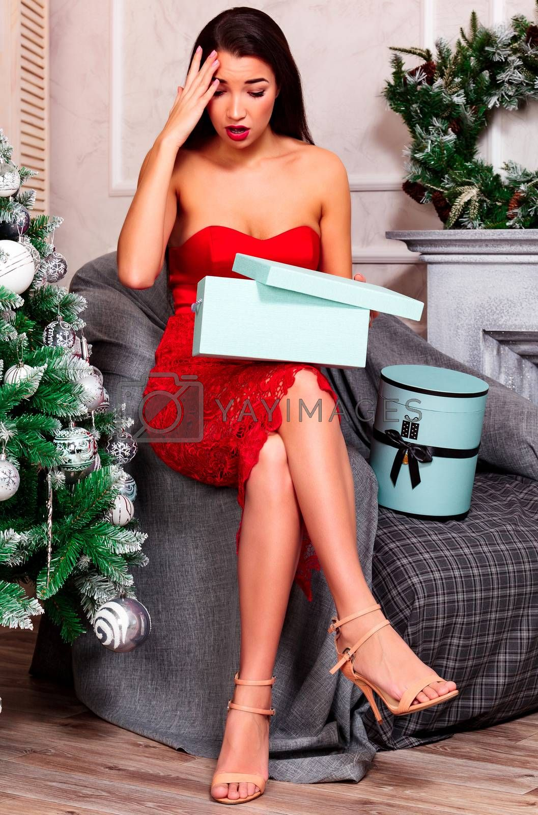 Unhappy and frustrated young woman holding gift box, christmas holidays concept