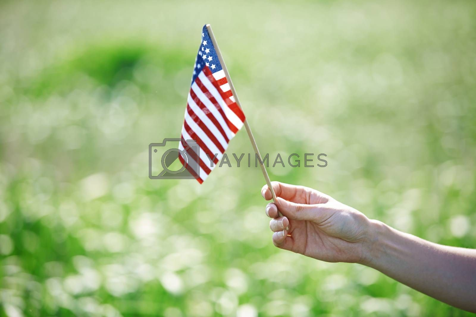 Human hand holding US flag for Independence Day