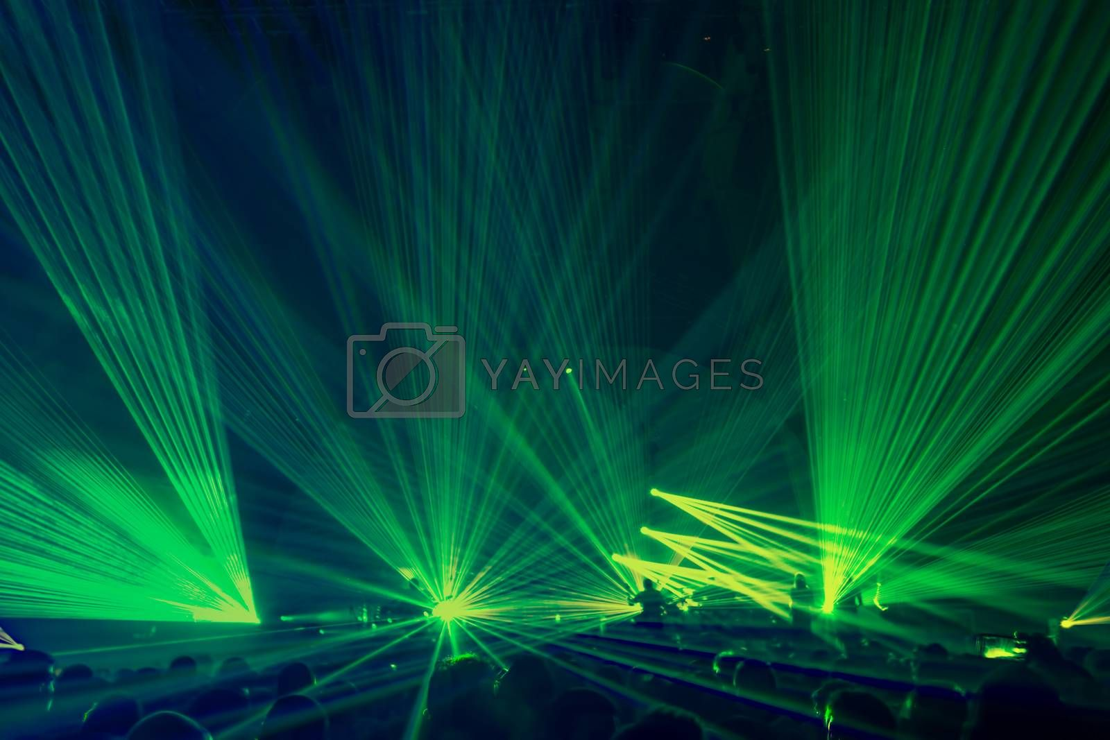 People on the party enjoying concert, dancing in the night club, celebrating new year eve, bright green laser light background