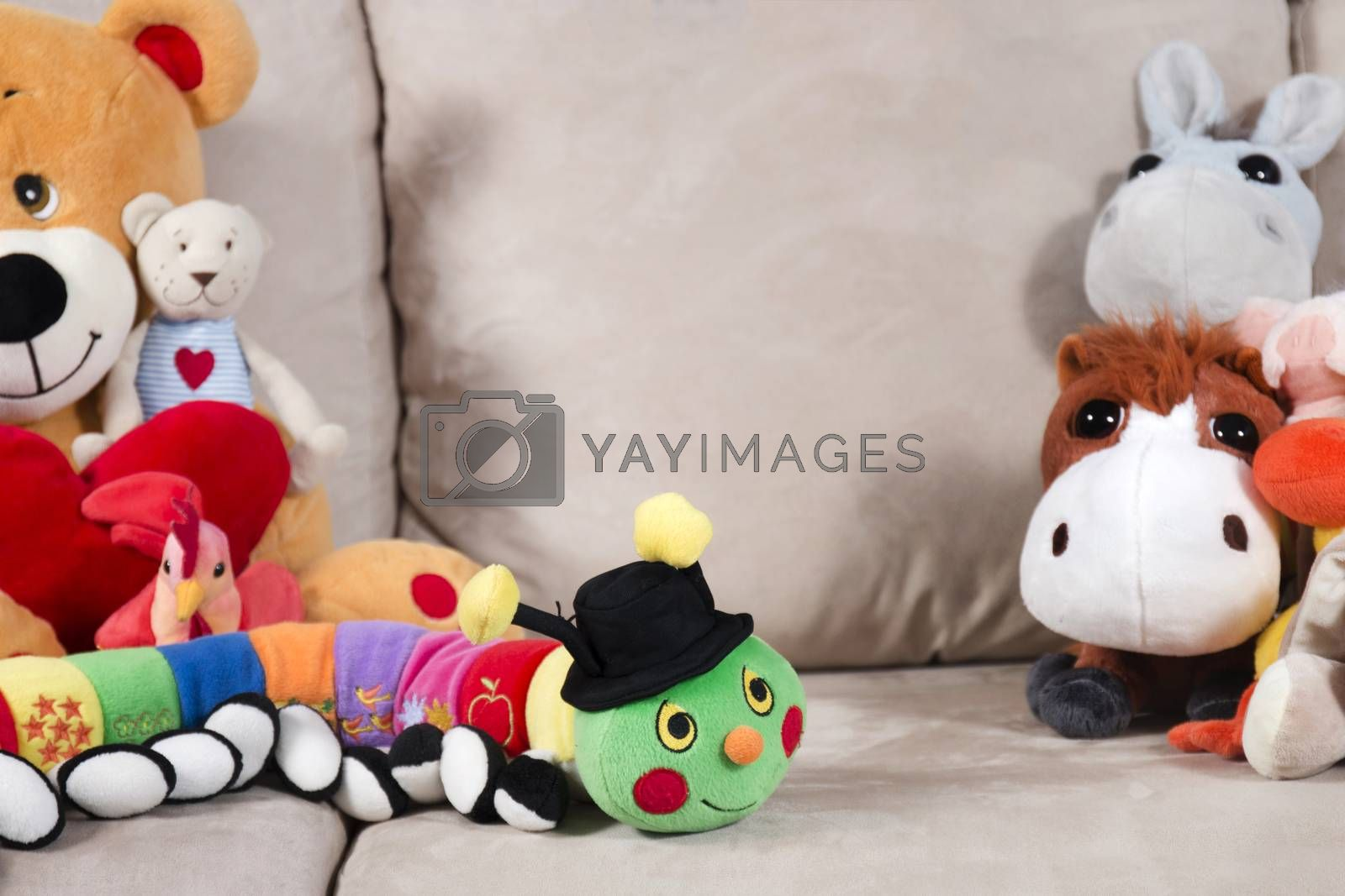 Group of stuffed toys on a sofa.