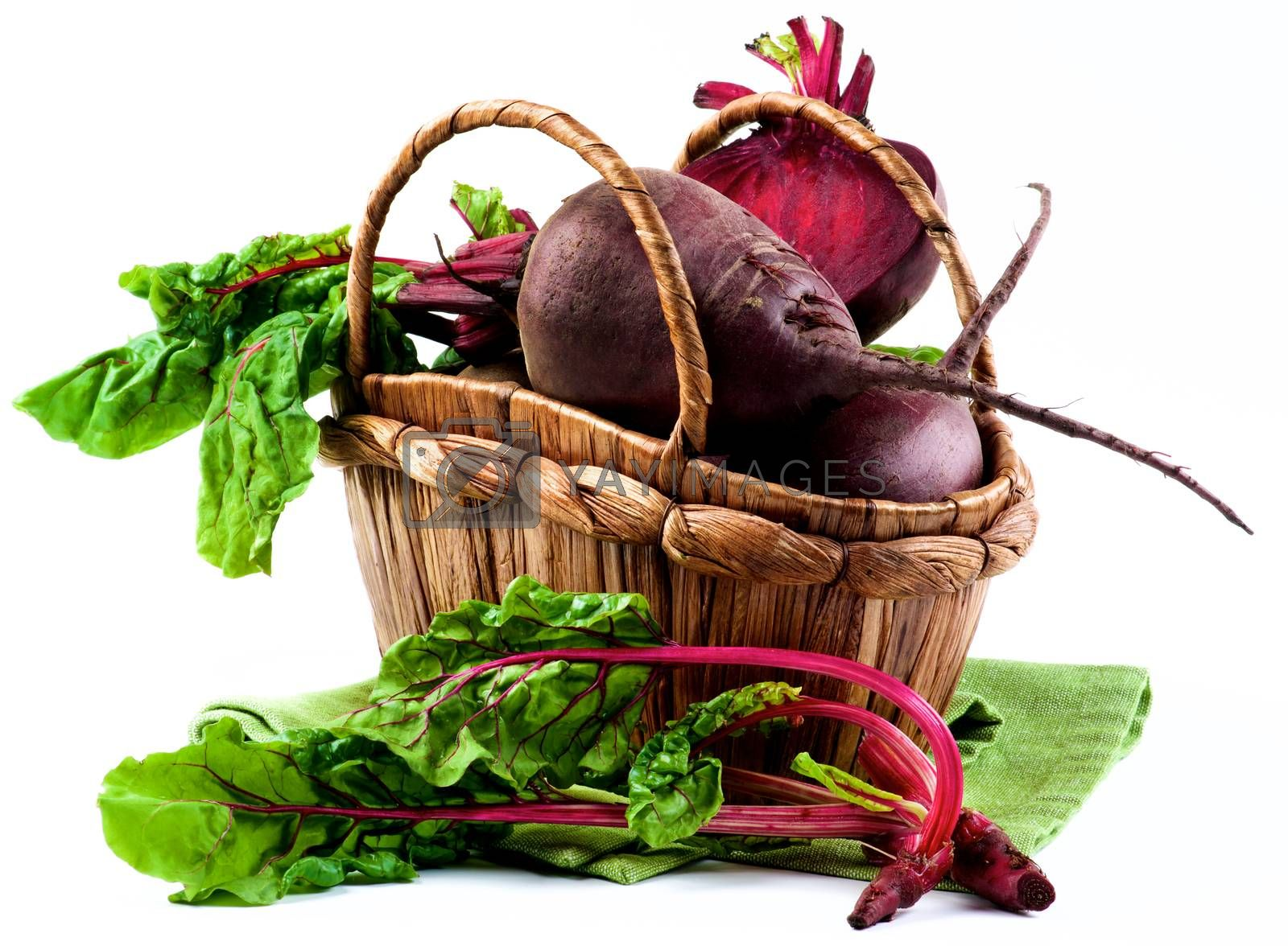 Arrangement of Full Body, Half and Young Sprouts with Green Beet Tops in Wicker Basket on Napkin isolated on White background