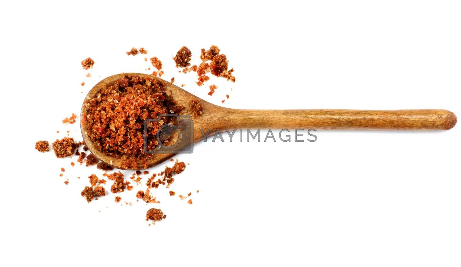 Homemade Salt with Dried and Crushed Sweet Red Paprika in Wooden Spoon isolated on White background