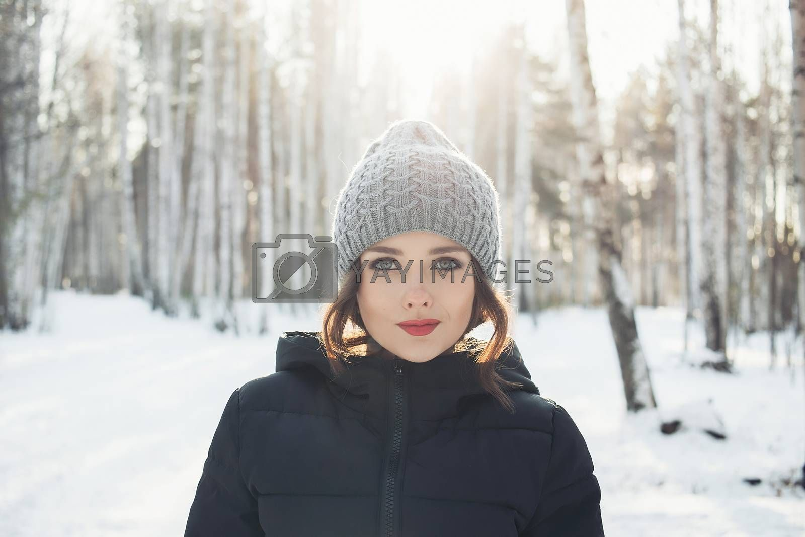 Beautiful young girl in a white winter forest.