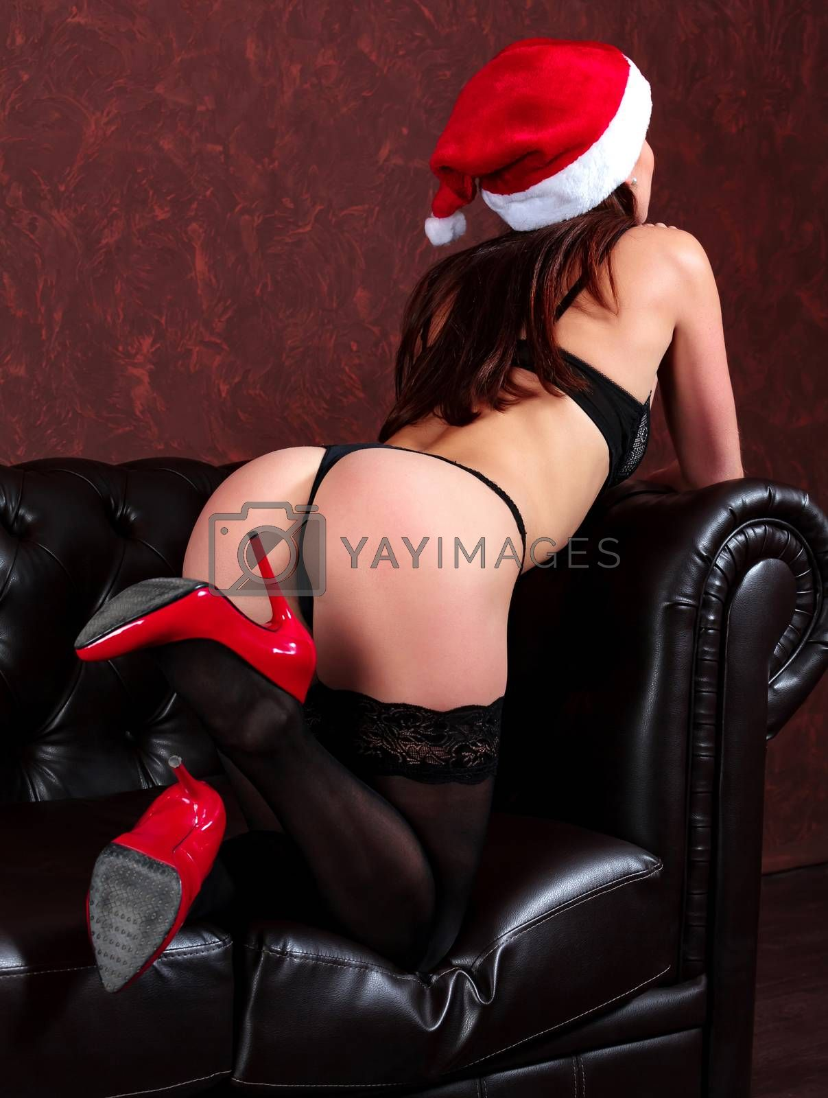 Sexy woman in black lingerie on a dark brown leather sofa. Christmas time concept