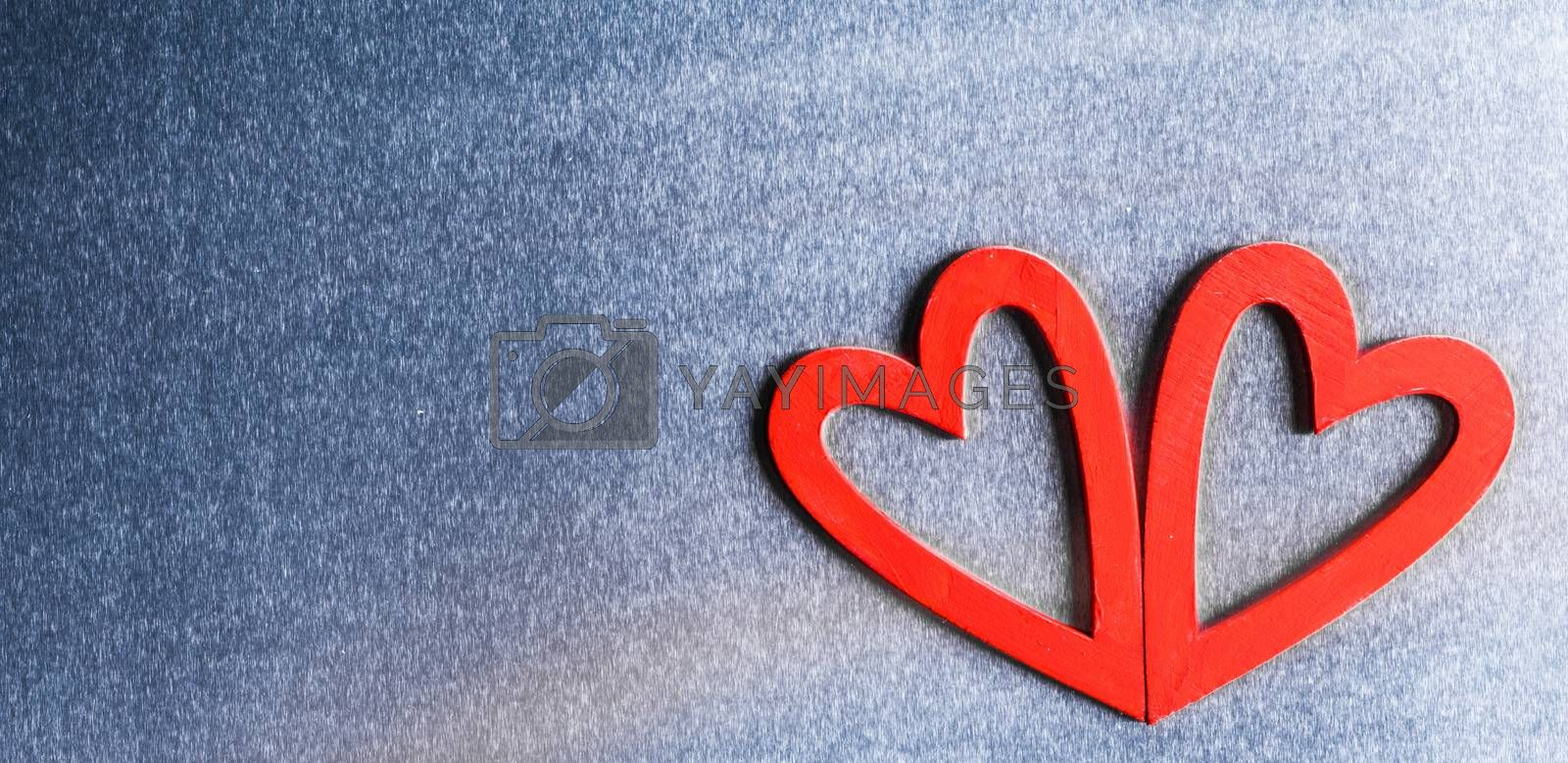 Two red wooden hearts on metal background with copy space