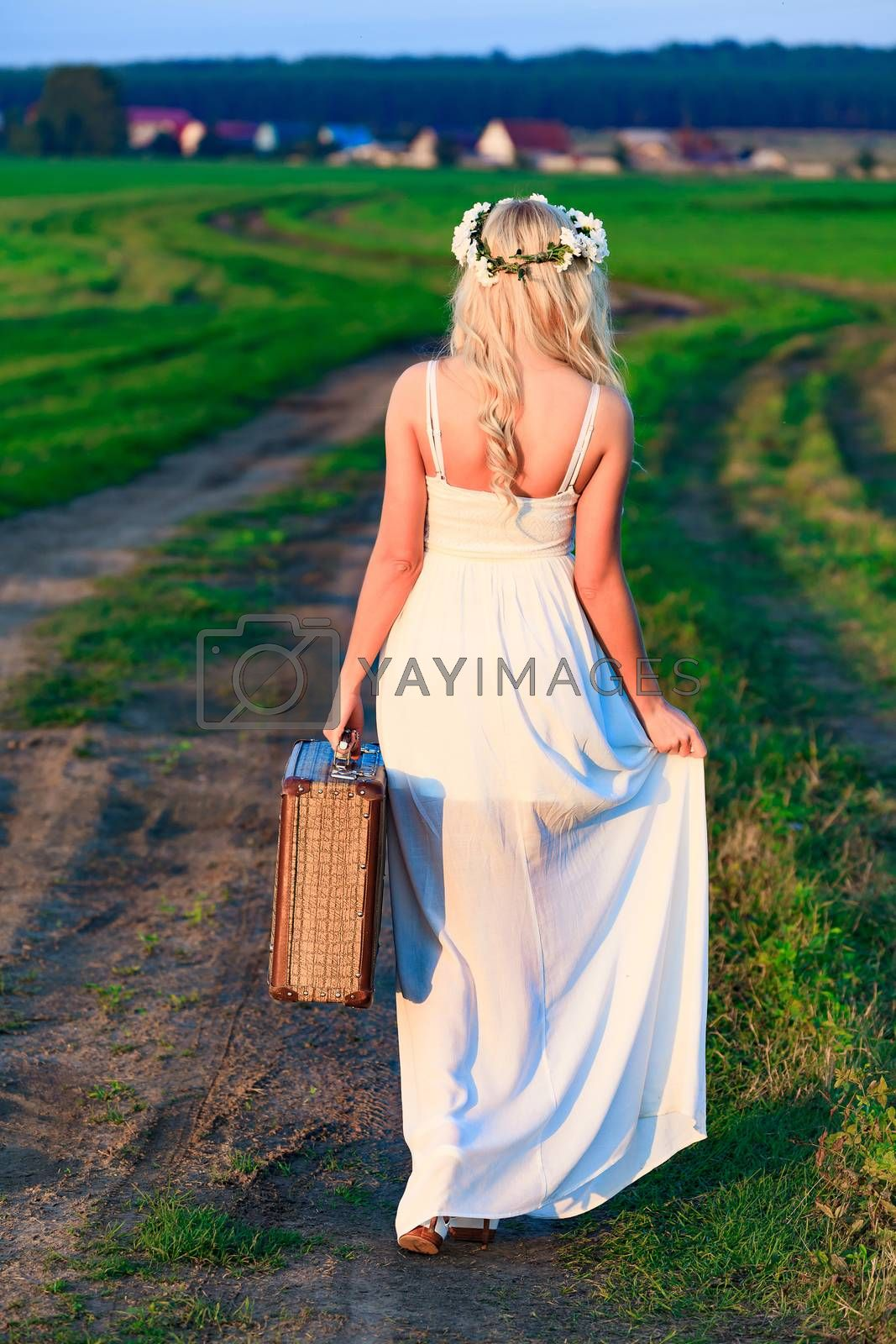 Blonde girl wearing white long dress with retro styled suitcase on countryside