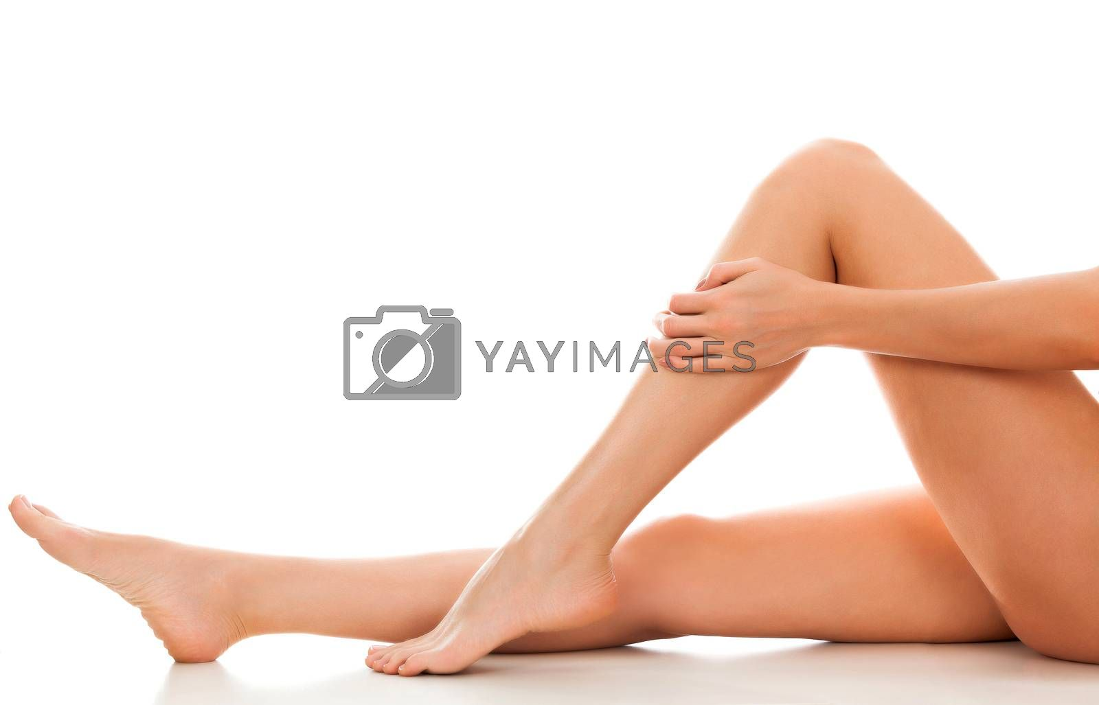 Beautiful smooth and shaved woman's legs. Isolated on white background. Skincare treatment concept