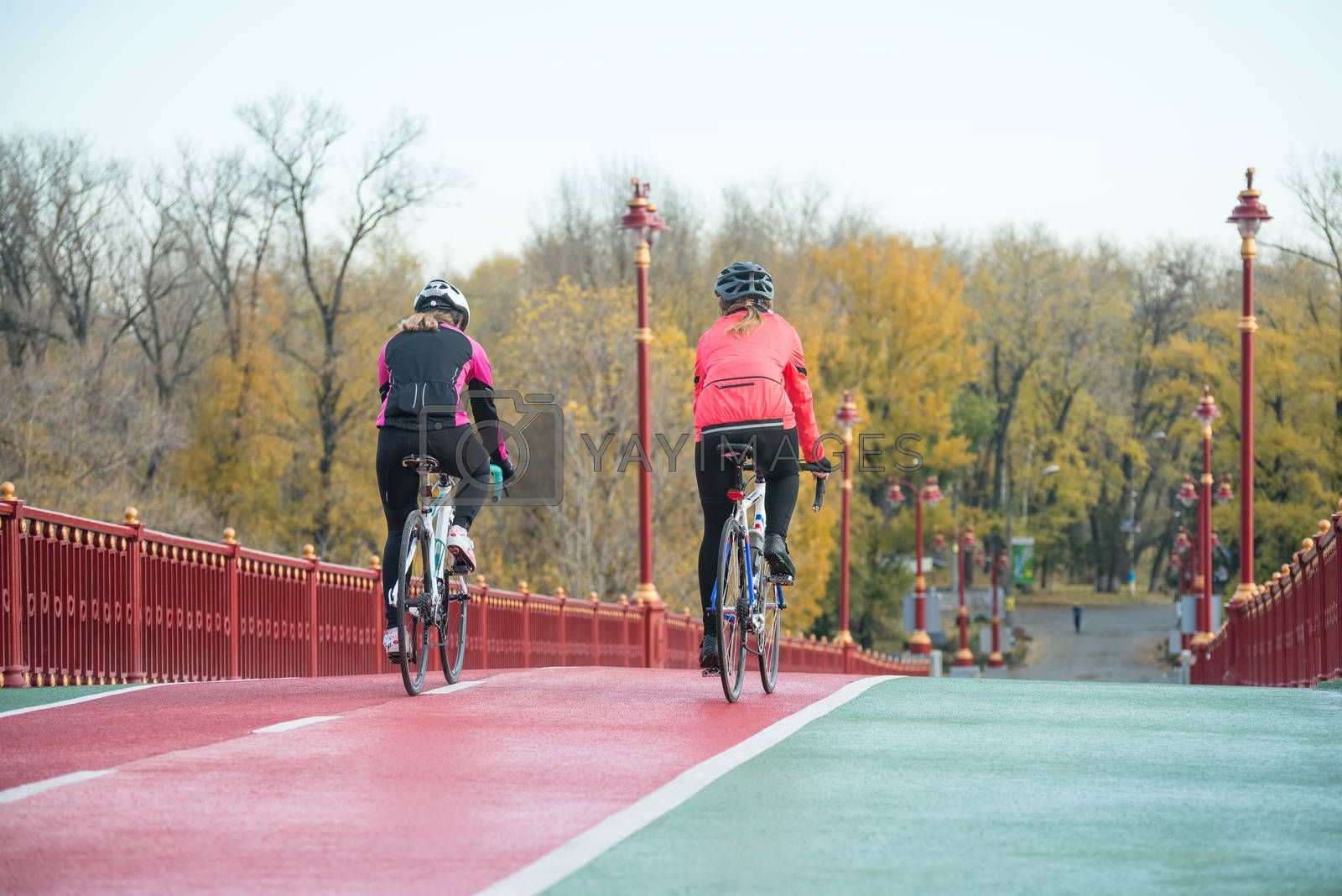 Two Young Female Cyclists Riding Road Bicycles on Bridge Bike Line in Cold Autumn Day. Healthy Lifestyle Concept. by maxpro