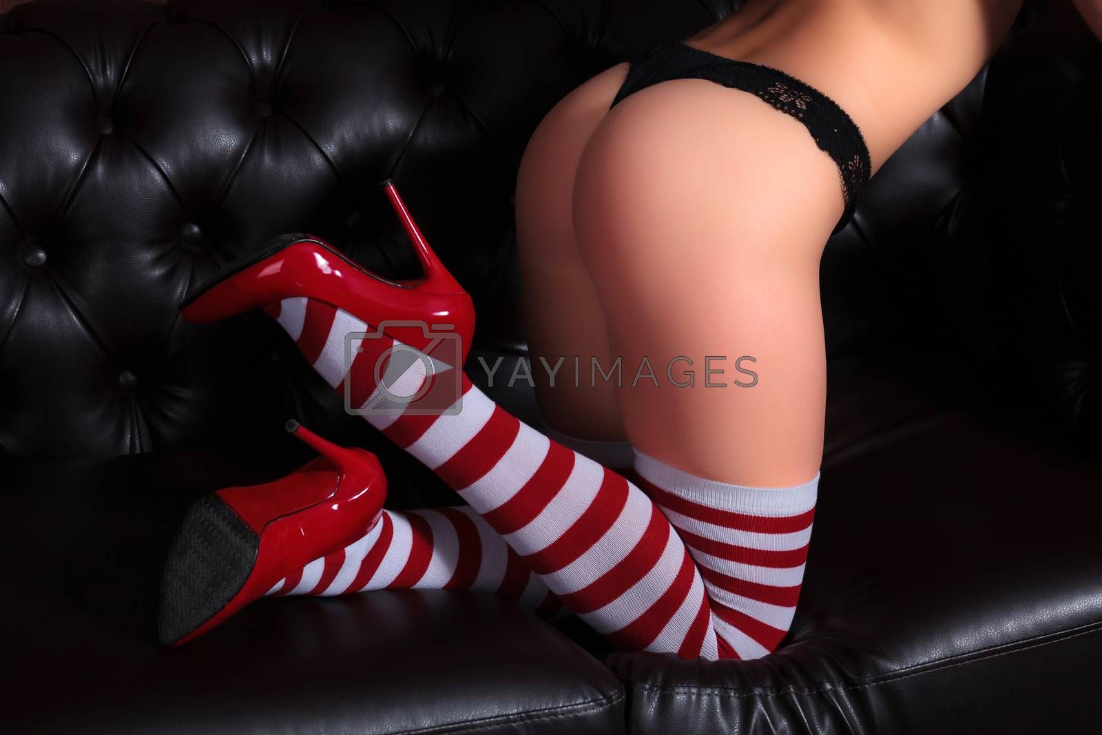 Closeup shot of beautiful female body, woman in striped tights and red shoes. Sexy lady posing on a brown leather sofa.