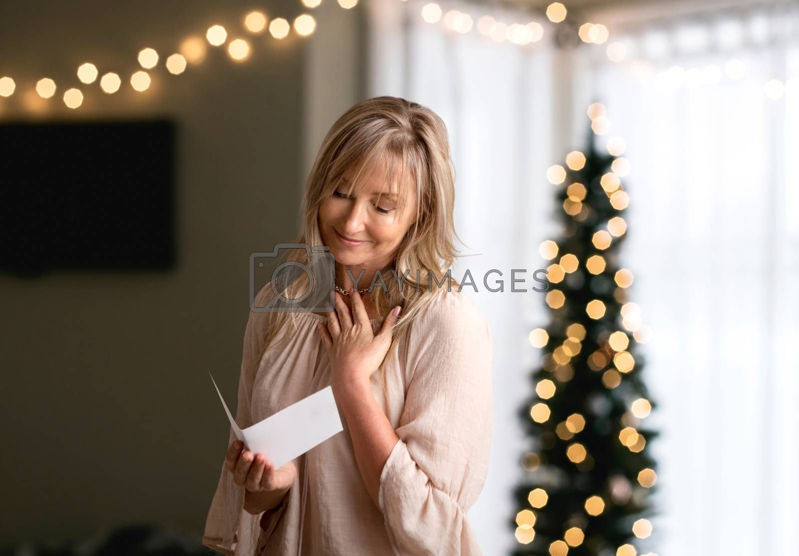 Woman reading a heartfelt message, note, book or card.   She is smiling and has her hand to heart.