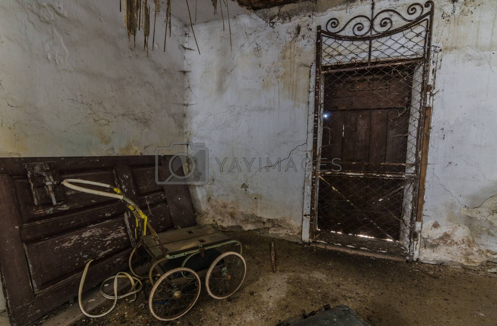 baby carriage in old abandoned cellar