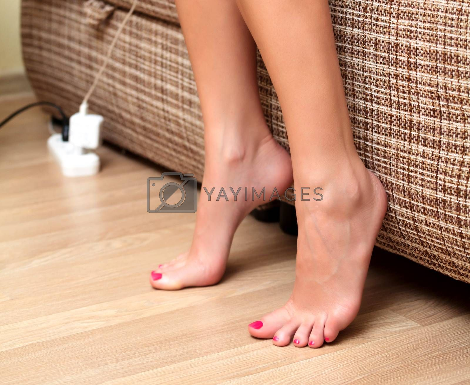 Closeup shot of female feet on the wooden floor beside a bed