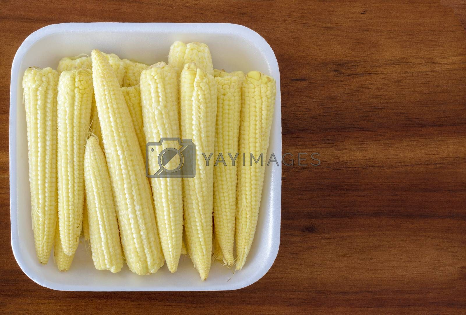Dish containing a stack of baby corn cobs on a wooden background