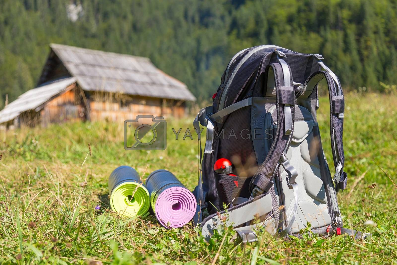 Royalty free image of Backpack and yoga mats on mountain meadow. by kasto