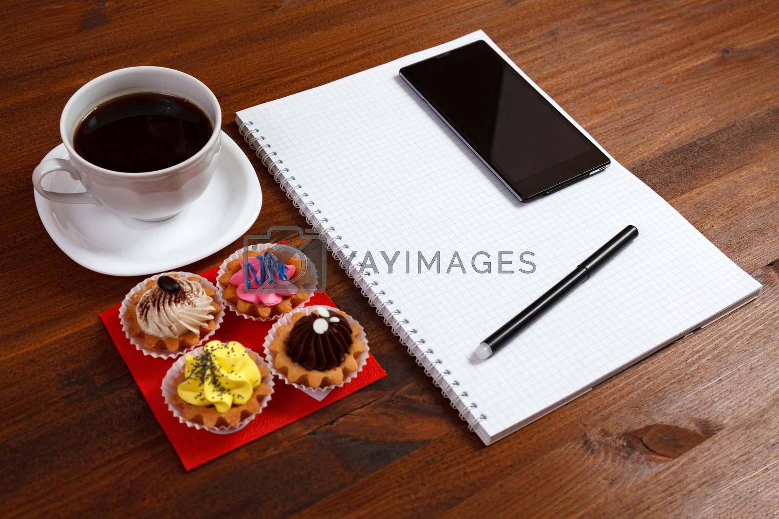 White coffee cup with notebook, four cupcakes, smartphone and pen on a wooden table.