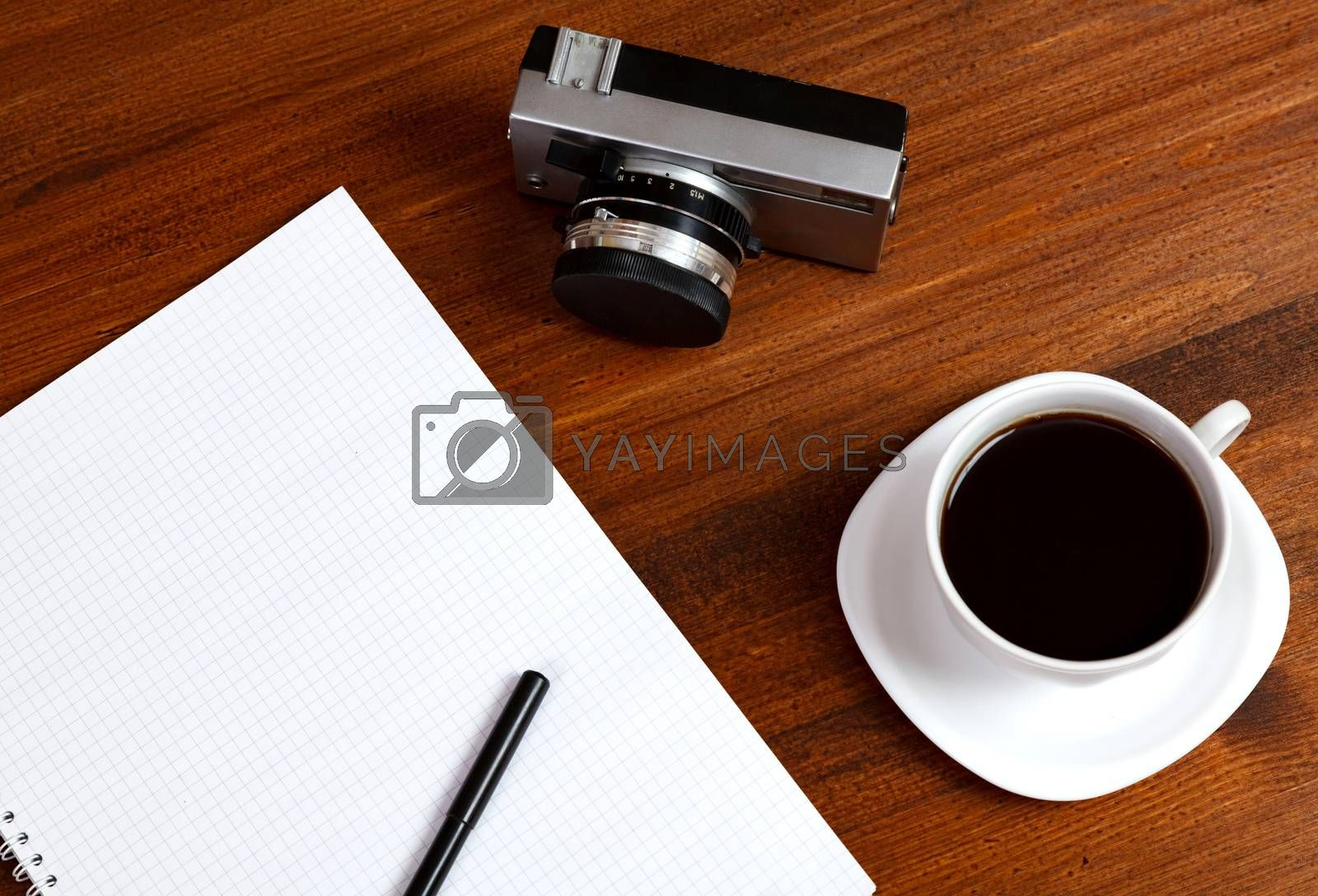 Retro film photo camera, cup of coffee and notebook with pencil on brown table. Top view.