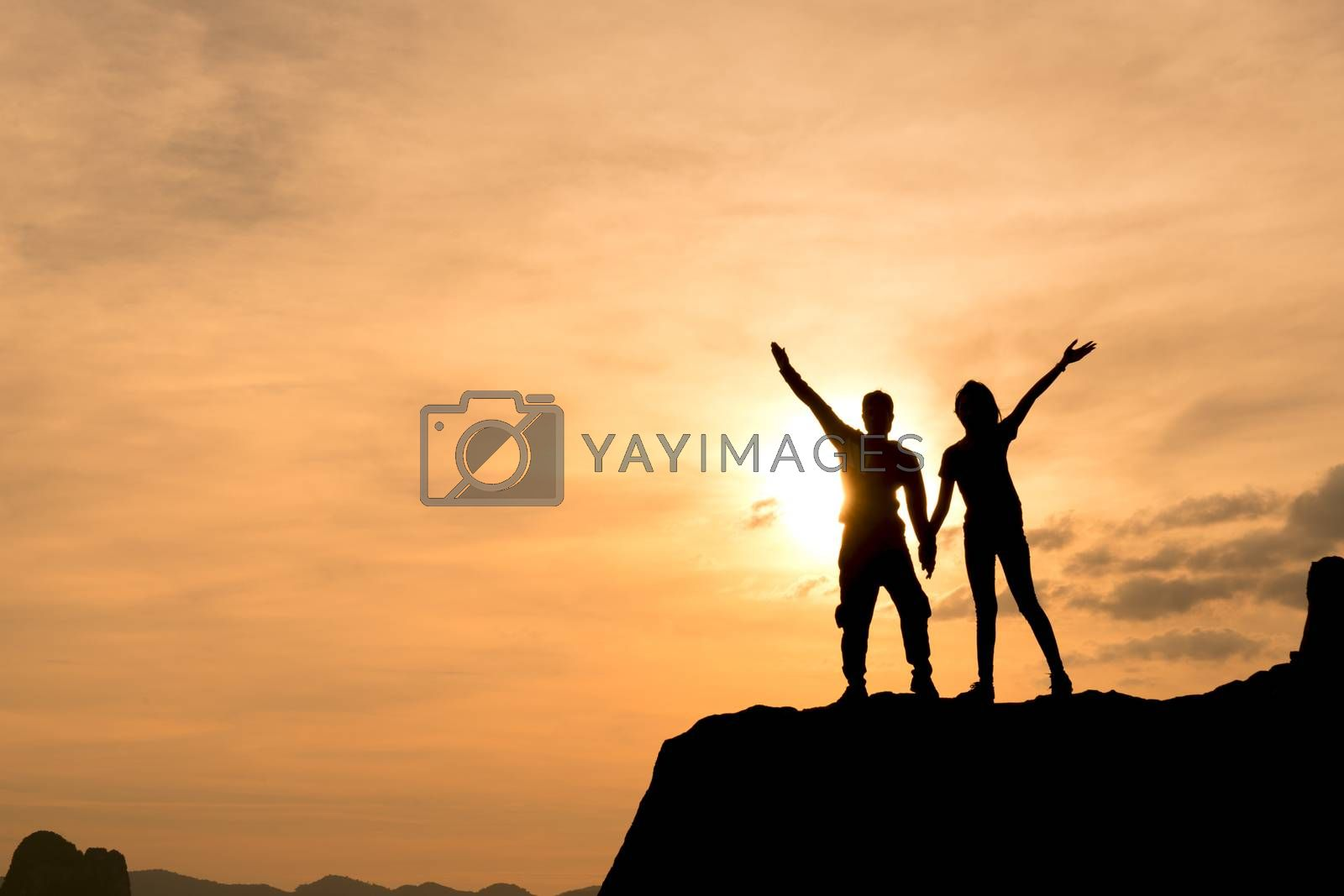 Succeeded in winning the sunset or sunrise, standing cheerfully with arms raised over the lovers' heads in celebration of reaching the top of the mountain peaks during trekking trips.