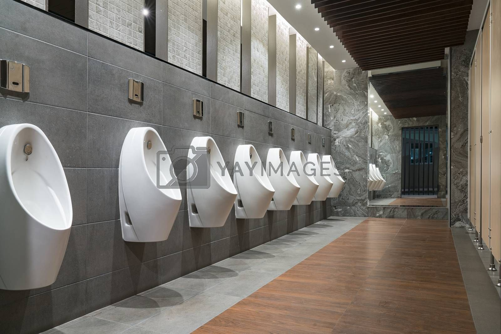 Closeup tile wall in human toilet with toilet, see by urinals and small room.