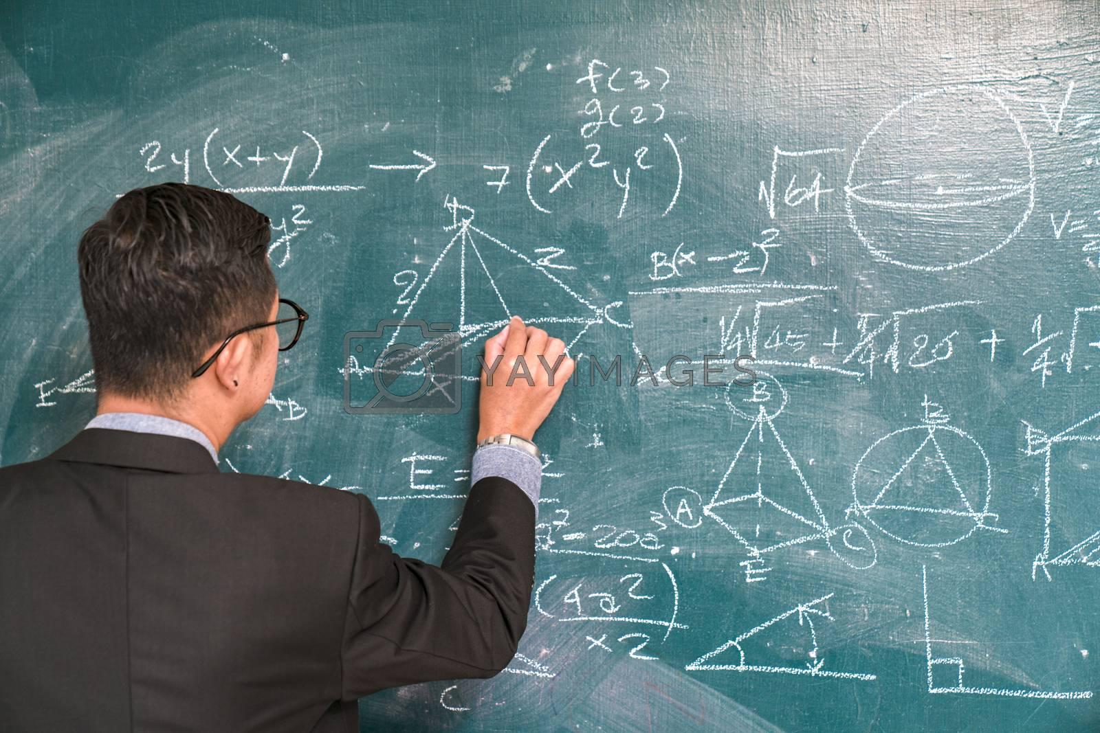 The science professor writes on the board while having a blackboard and a blackboard.