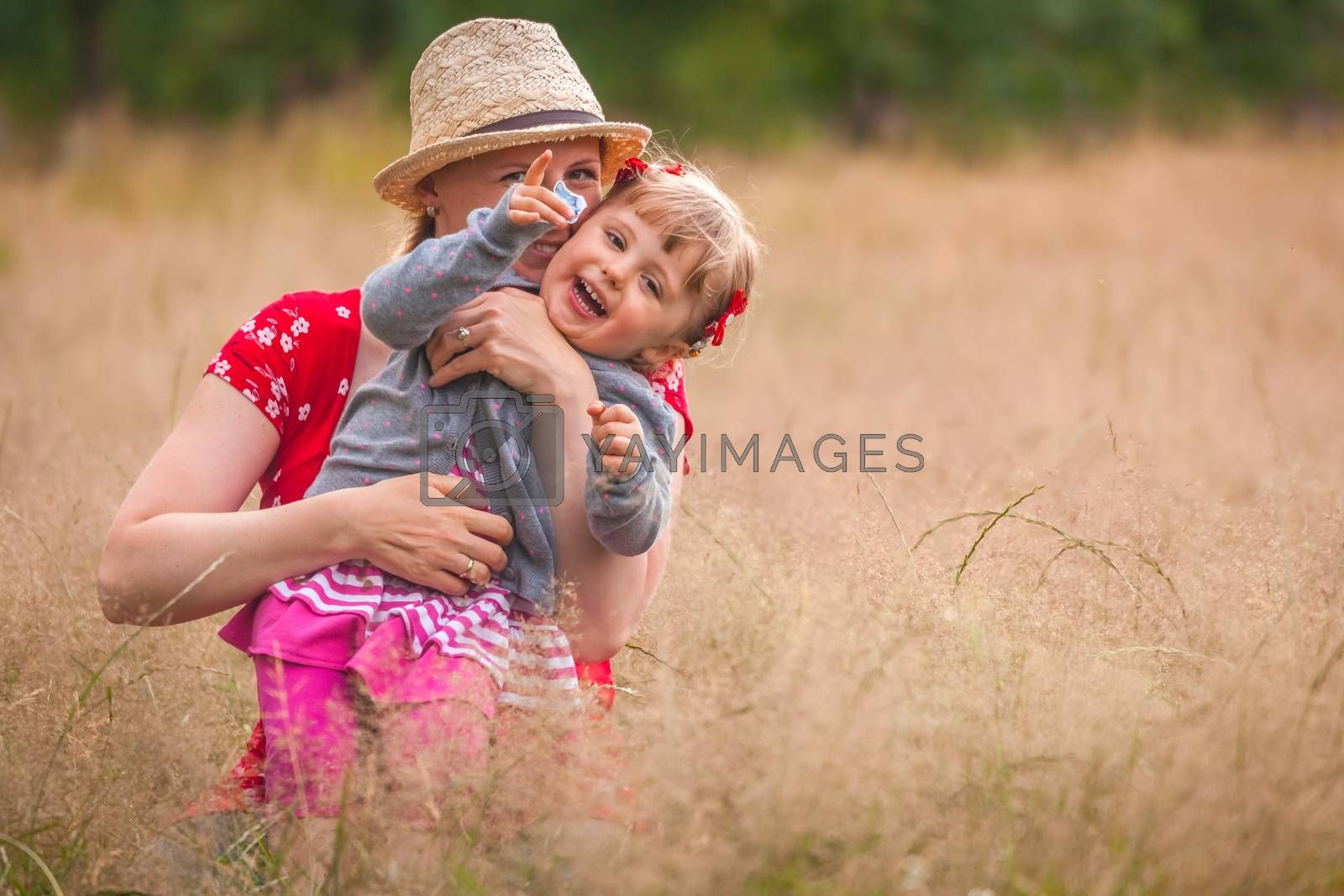 Mother and daughter playing together on a meadow