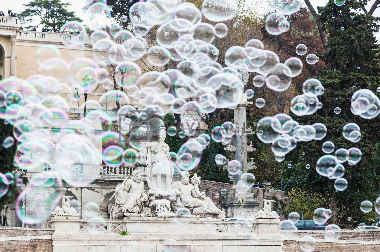 Group of flying soap bubbles covering fountain named Rome between the Tiber and the Aniene in Piazza del Popolo in Rome, Italy