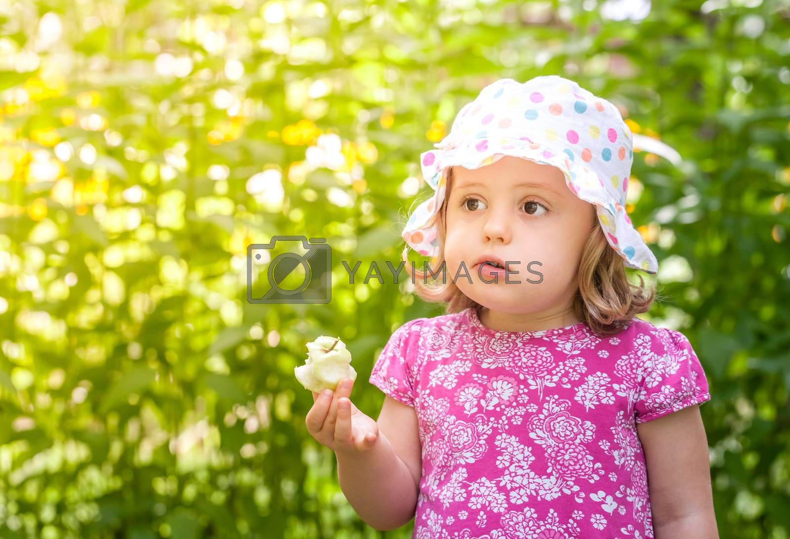Cute little girl eating freshly picked apple