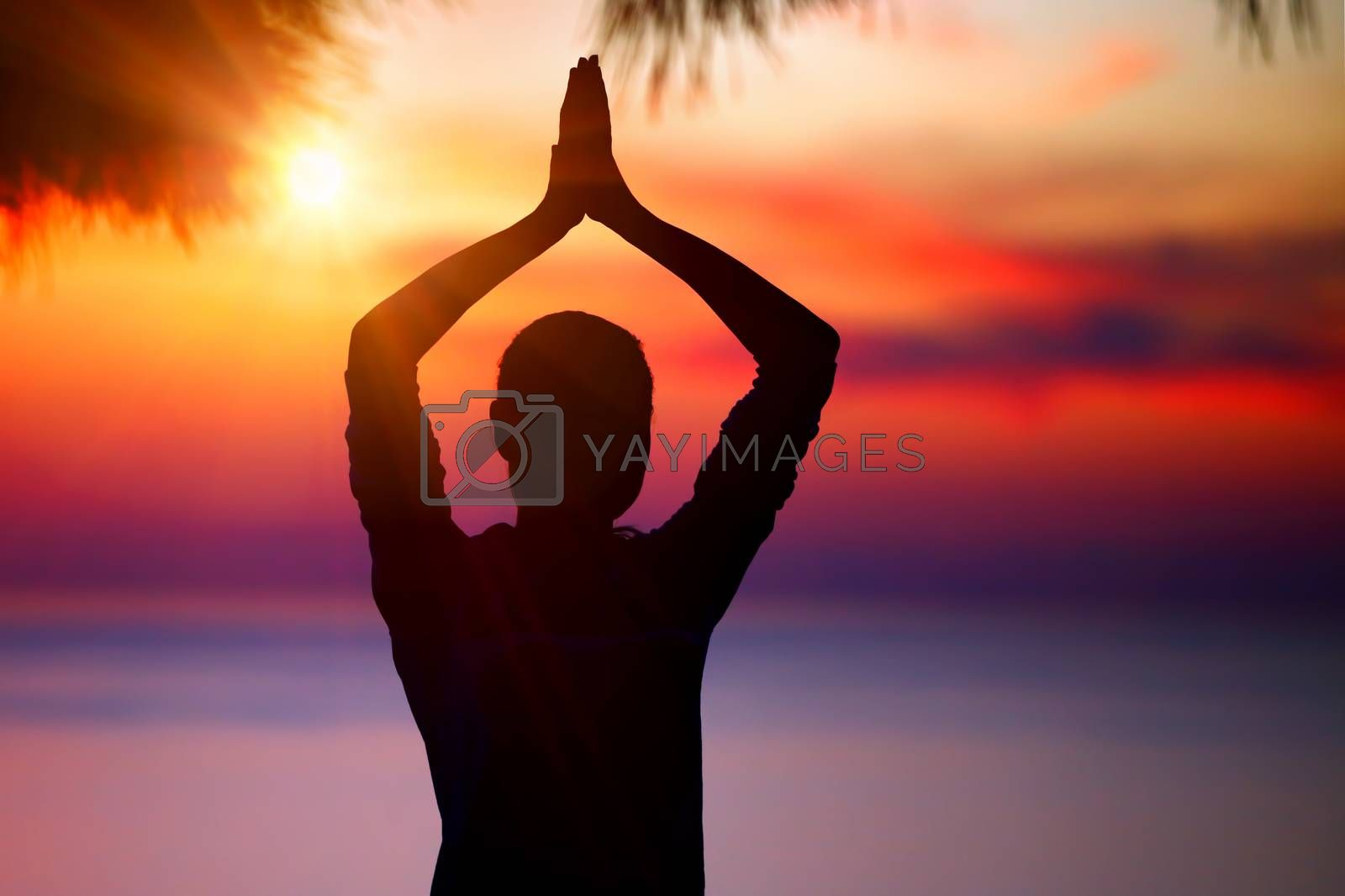 Silhouette of a woman doing yoga posture over colorful sunset background, meditation outdoors, mental health, healthy lifestyle concept