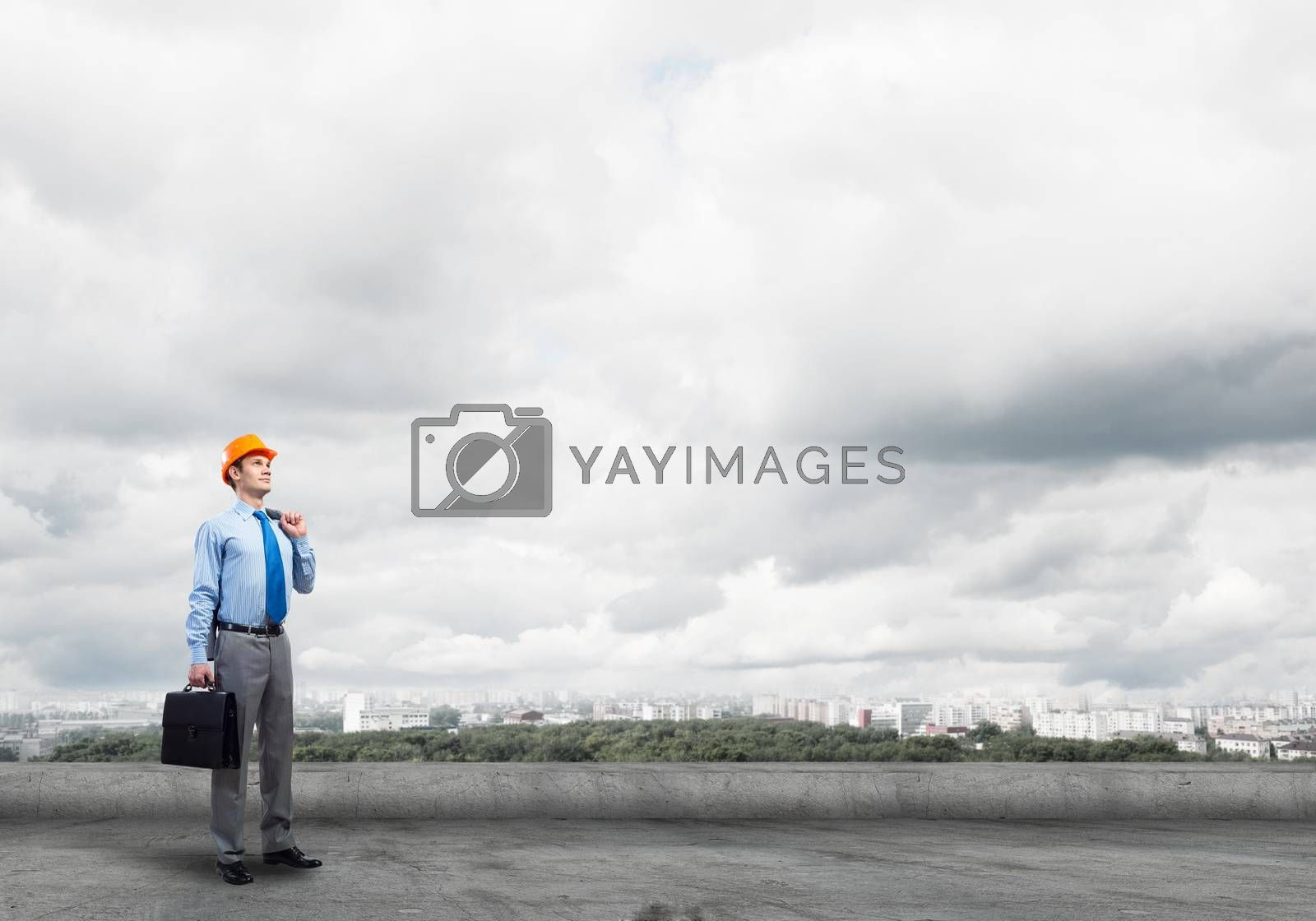 Young handsome man architect in hardhat with project in hand