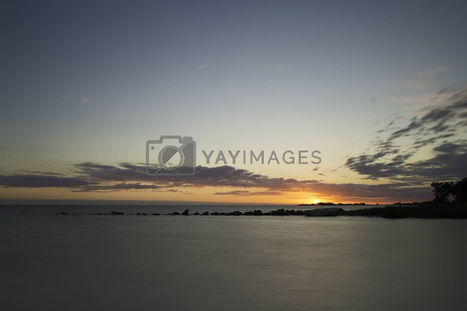 Sunset over Ocean with Breakwater and rowboat in Gotland, Sweden.