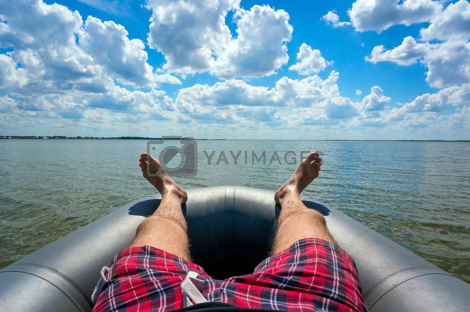 A young man lies resting on the gray inflatable boat on the lake. Relax outdoors and fishing on the background of beautiful sky with white Cumulus clouds