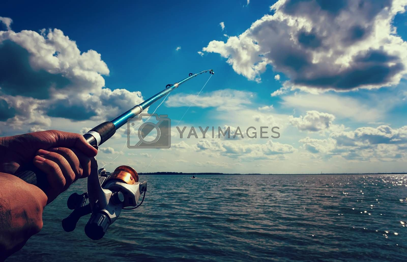 hand holding a fishing rod with reel. Focus on Fishing Reels. Toned image