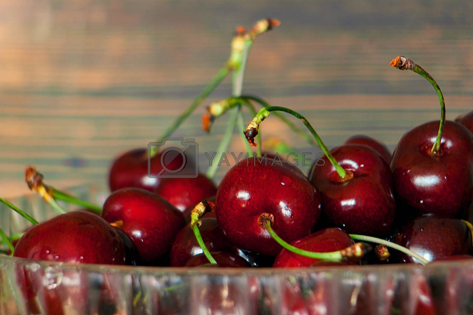 Fresh cherries in jar on the wooden background. Selective focus. Focus on the right cherries in front of jar.